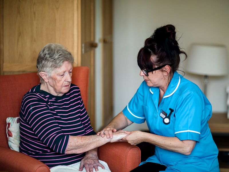 Carer giving hand massage to resident